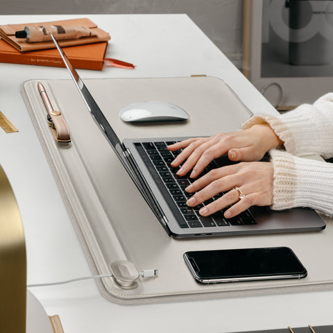 An Orbitkey Desk Mat (a rectangular stone-coloured mat laid on a desk) with a laptop, phone, and mouse resting on it as a pair of hands type at the laptop keyboard