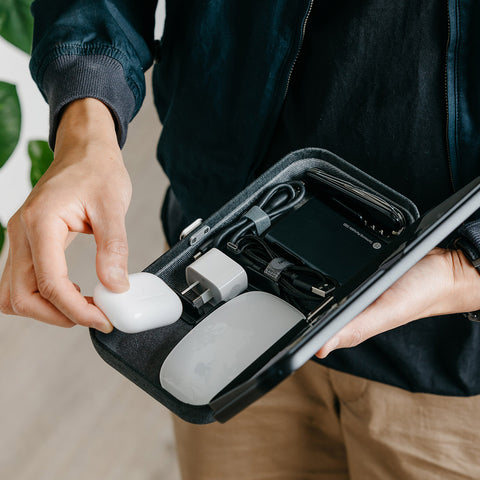 Orbitkey Nest Desk Organiser | Milligram [img: an Orbitkey Nest with its top open, held in one hand as another puts an AirPor case inside alongside an Apple mouse, USB charger and sundry cables]