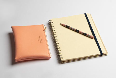 A Delfonics notebook lays open on a grey surface, a pen laid across its exposed Grid page. Next to it, a peach-coloured wallet.