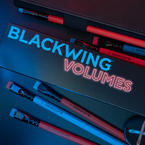 Blackwing's Volume 6 pencils in lurid orange and blue, loose on a dark surface around the box the pencils come in (also black, with Blackwing Volumes written on it in equally bright orange and blue lettering)