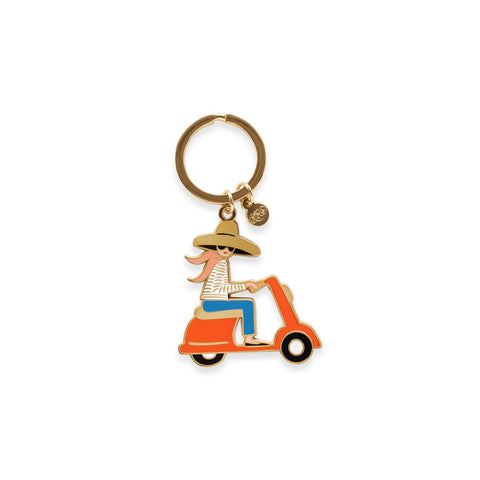 Rifle Paper Co.'s Scooter Enamel Keyring, featuring a cute design of a redheaded woman riding a Vespa-style scooter