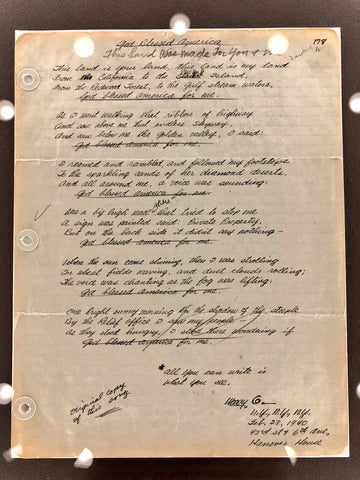 A photo of Woody Guthrie's handwritten lyric sheet for the song that would become This Land Is Your Land, displayed behind glass