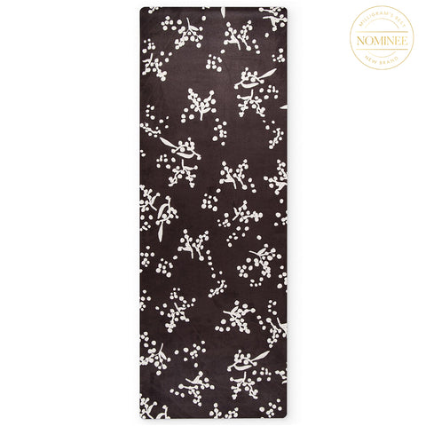 A yin yoga mat in the Watl print, which features plantlike white forms on black background