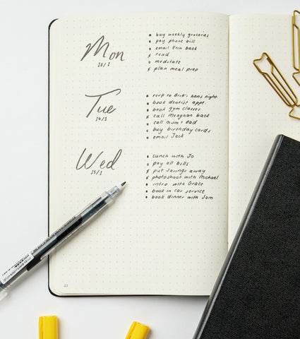 An image of an open dot grid notebook with Mon Tues Wed to-do lists