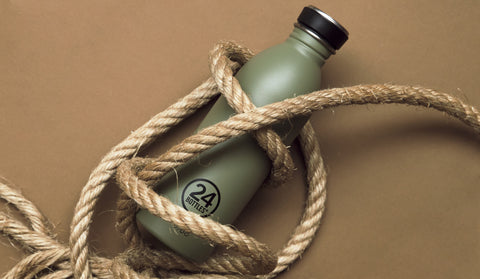 A 24Bottles Urban Drink Bottle in Sage, wrapped loosely in a coarse rope
