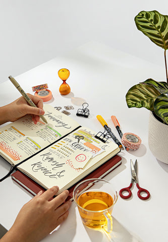 An open bullet journal notebook full of writing and designs, sat on a desk surrounded by markers, washi tape, scissors and more stationery