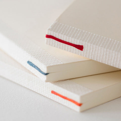 A close-up of three Midori notebooks stacked loosely on top of each other, each with an exposed cheesecloth tape on the spine