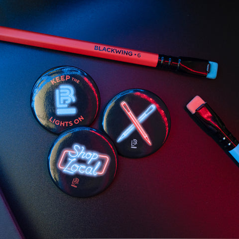 Blackwing Volume 6 button set (a group of 3 small circular pin badges with black backgrounds and neon illustrations) laid on top of a black notebook cover with orange and blue Volume 6 pencils laid around