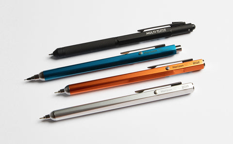 img: four OHTO pens laid parallel; one black, one blue, one orange, one silver