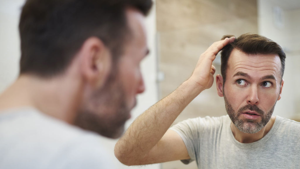 DHEA hair loss guy worried in front of mirror