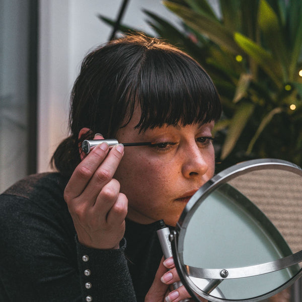 a woman using eyelash growth serum in front of a mirror