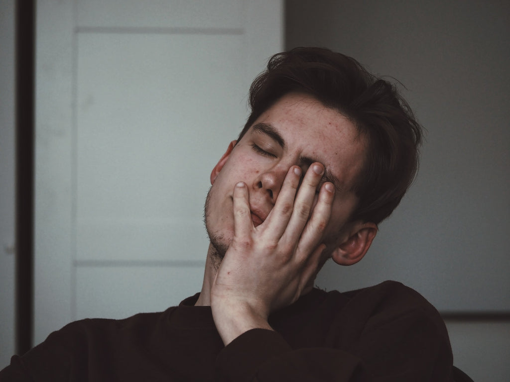 guy sitting tired with hand on face