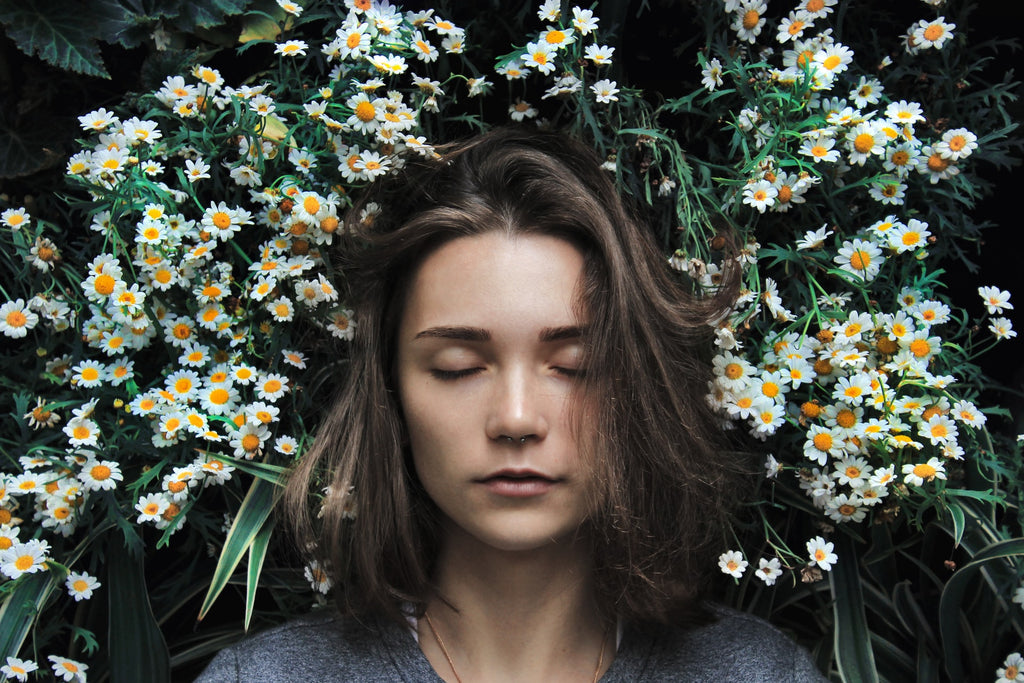 woman standing eyes closed on a flowerbed