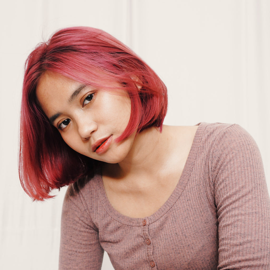 asian woman with dyed hair looking at camera