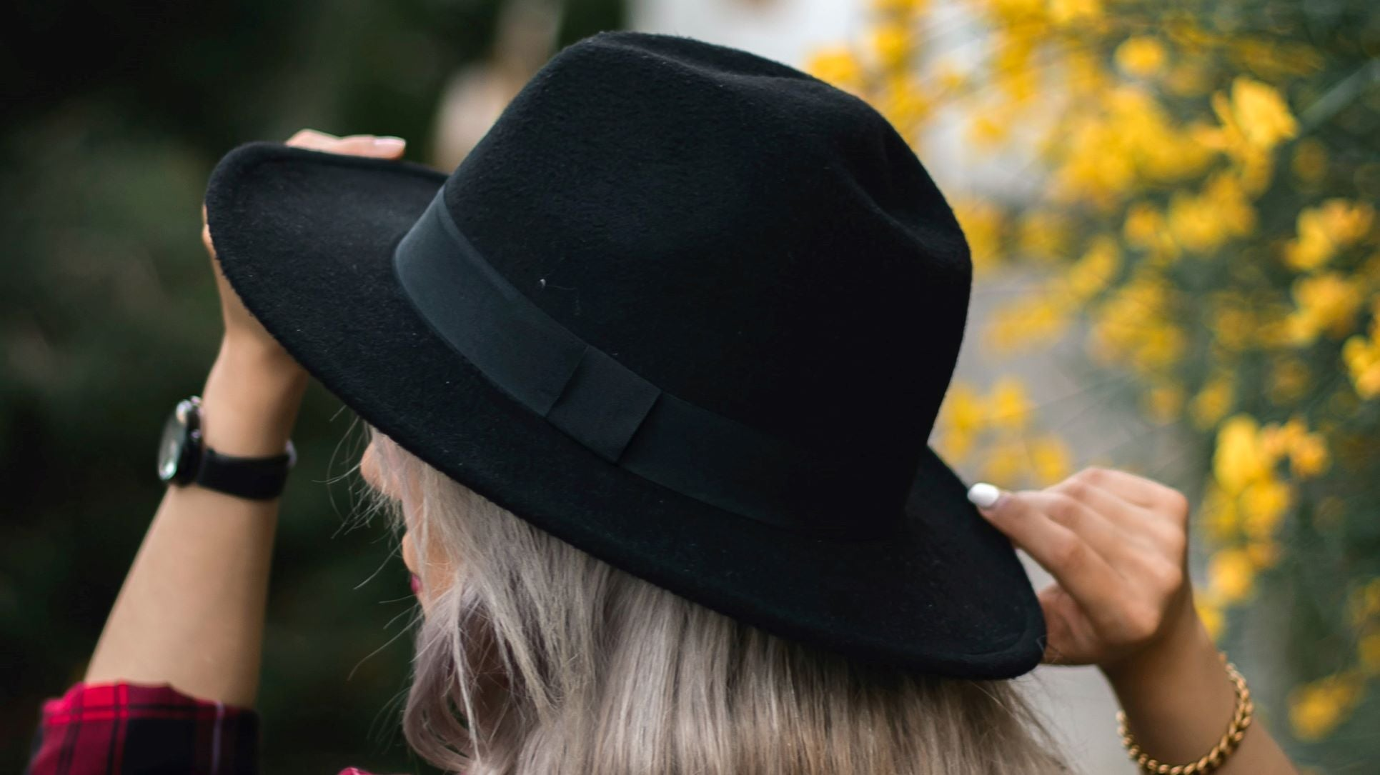 a woman wearing a fedora hat on suburb background