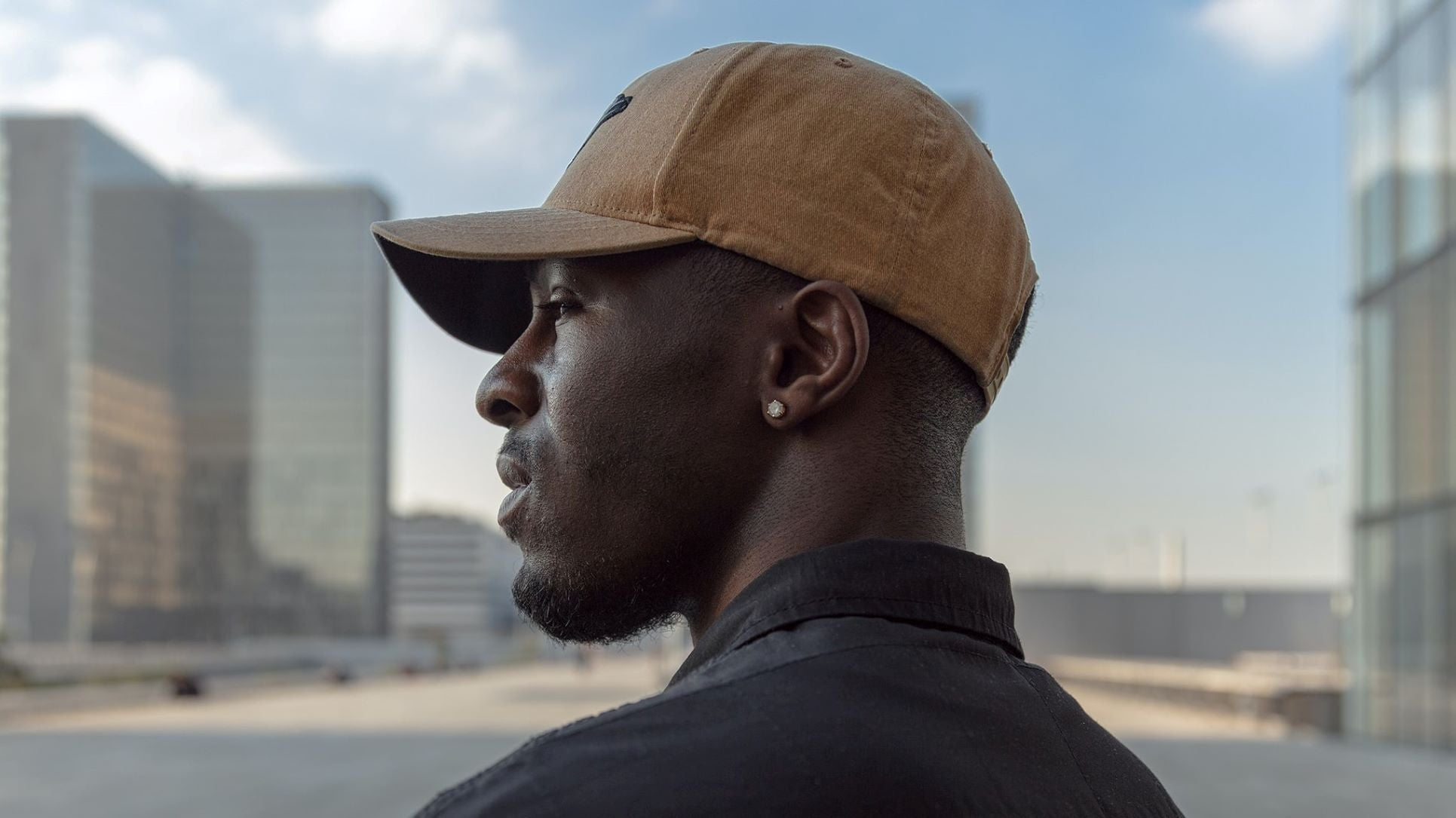 a dark man wearing a cap hat on city background, looking bald