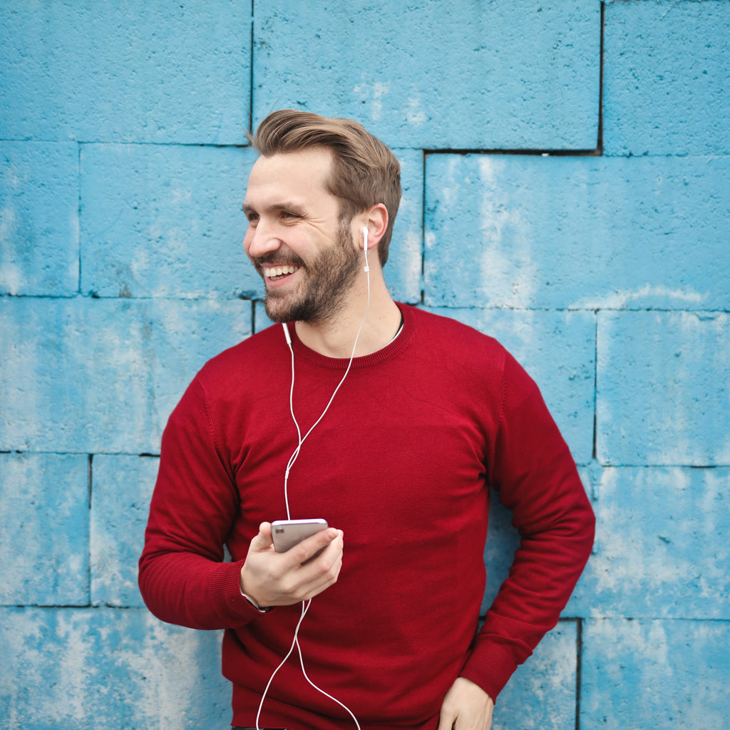 mature hairline guy back against wall, with headphones and red shirt