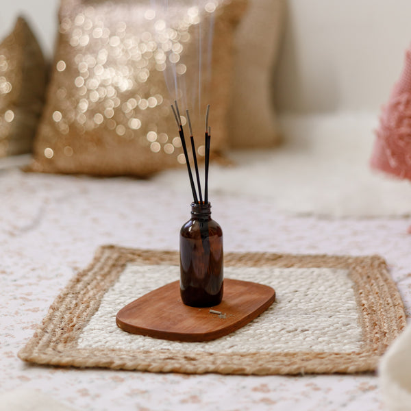Fragrance bottle on a rope mat, chic background.