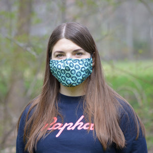 woman wearing blue floral face mask in a forest