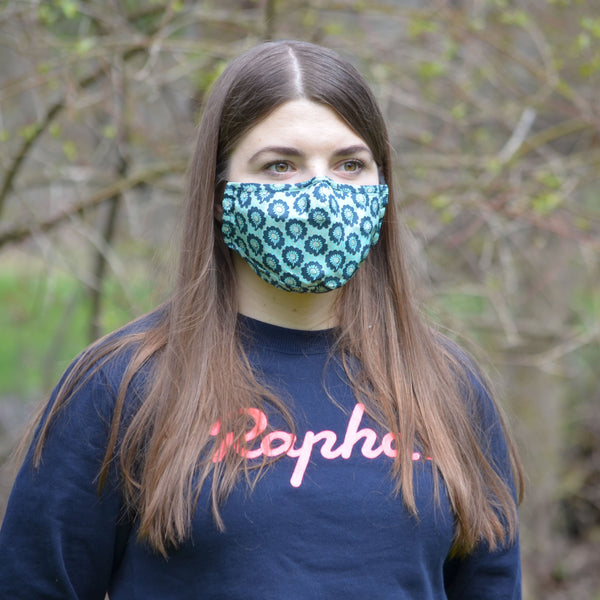 woman wearing blue floral face mask in a forest looking left