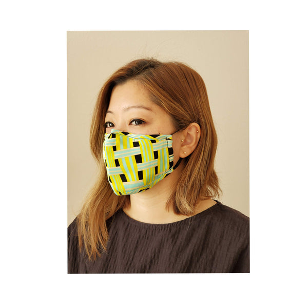 woman looking to the right while wearing neon green face mask