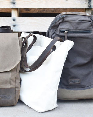 a saddle bag, canvas tote, and backpack