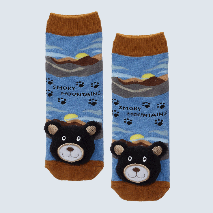 Two socks against a white background. The socks feature the Great Smoky Mountains and a plush bear charm on each toe.
