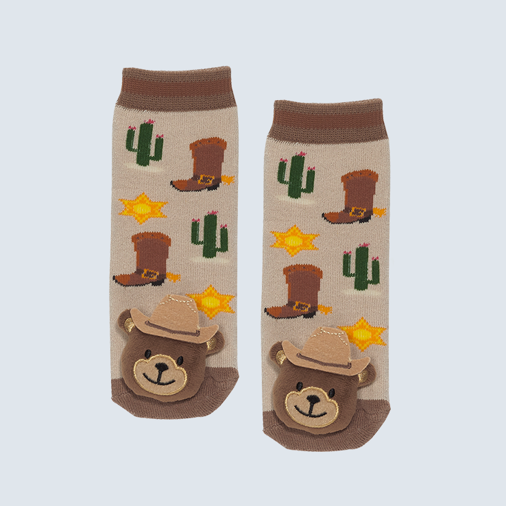 Two socks against a white background. The socks feature cowboy boot and cactus motifs with a cute plush bear charm on the toe.
