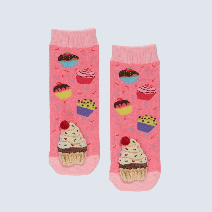 Two socks against a white background. The socks feature cupcakes and a cute plush on each toe.
