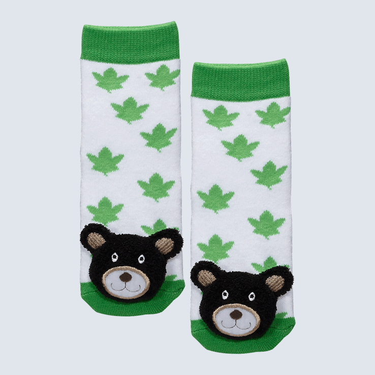 Two socks against a white background. The socks feature white and green maple leaf motifs and a cute plush bear charm on each toe.