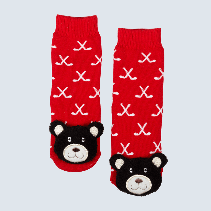 Two socks against a white background. The socks feature a red and white hockey stick motif and a cute plush bear charm on the toe.