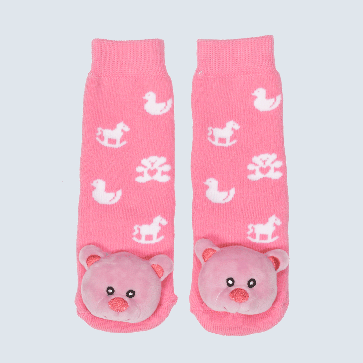 Two pink socks against a white background. The socks feature a toy motifs and a cute plush bear charm on the toe.