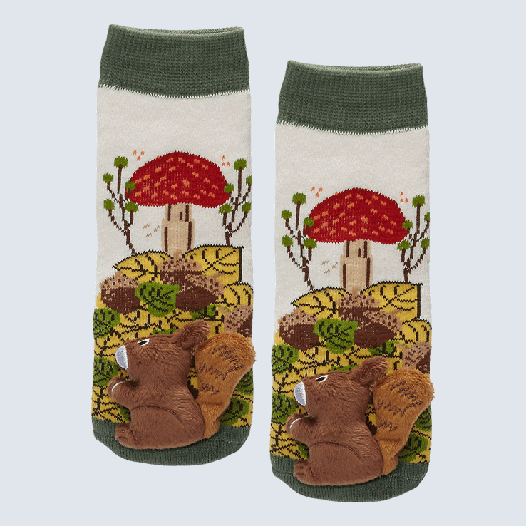 Two socks against a white background. The socks feature a mushroom and nature pattern. Each sock has a  cute plush squirrel charm on the toe.