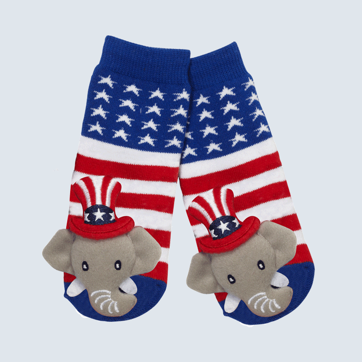 Two socks against a white background. The socks feature an American flag pattern and a cute plush elephant charm on the toe.