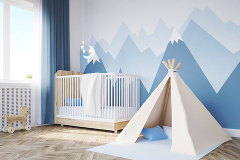 Child's bedroom in shades of blue with a canvas teepee in front of a crib
