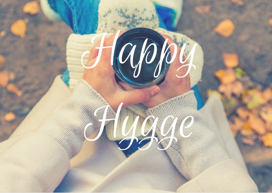 Image of woman holding a cup with the word Hygge superimposed
