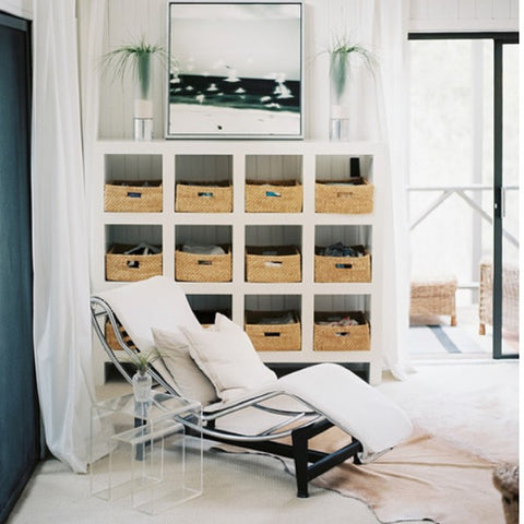 White lounge chair in a living room with a 16 cube storage solution featured