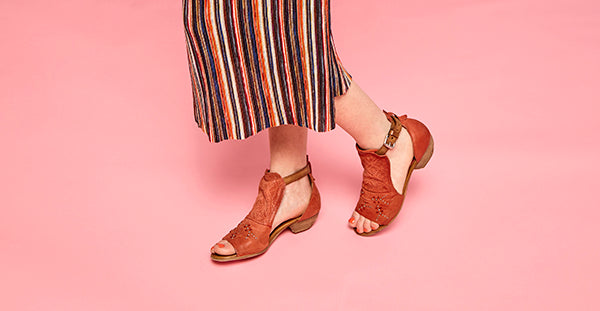 Girl modeling Carey sandals in tomato colour