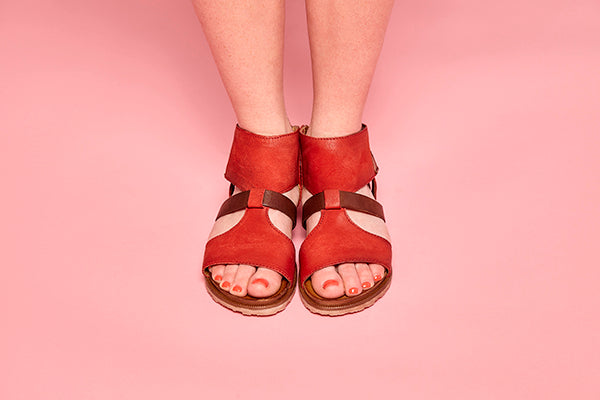 Woman modeling Tamsyn sandals in tomato colour