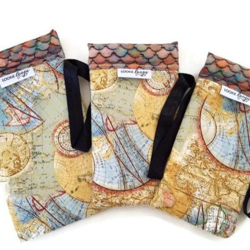 Old world atlas print sunglass and cell phone case called Lookie Loops. 3 sizes shown, each with an elastic loop for attaching to a bag or strap. Band and interior are a tile roof print.  Primary color tan with gold metallic thread running throughout.