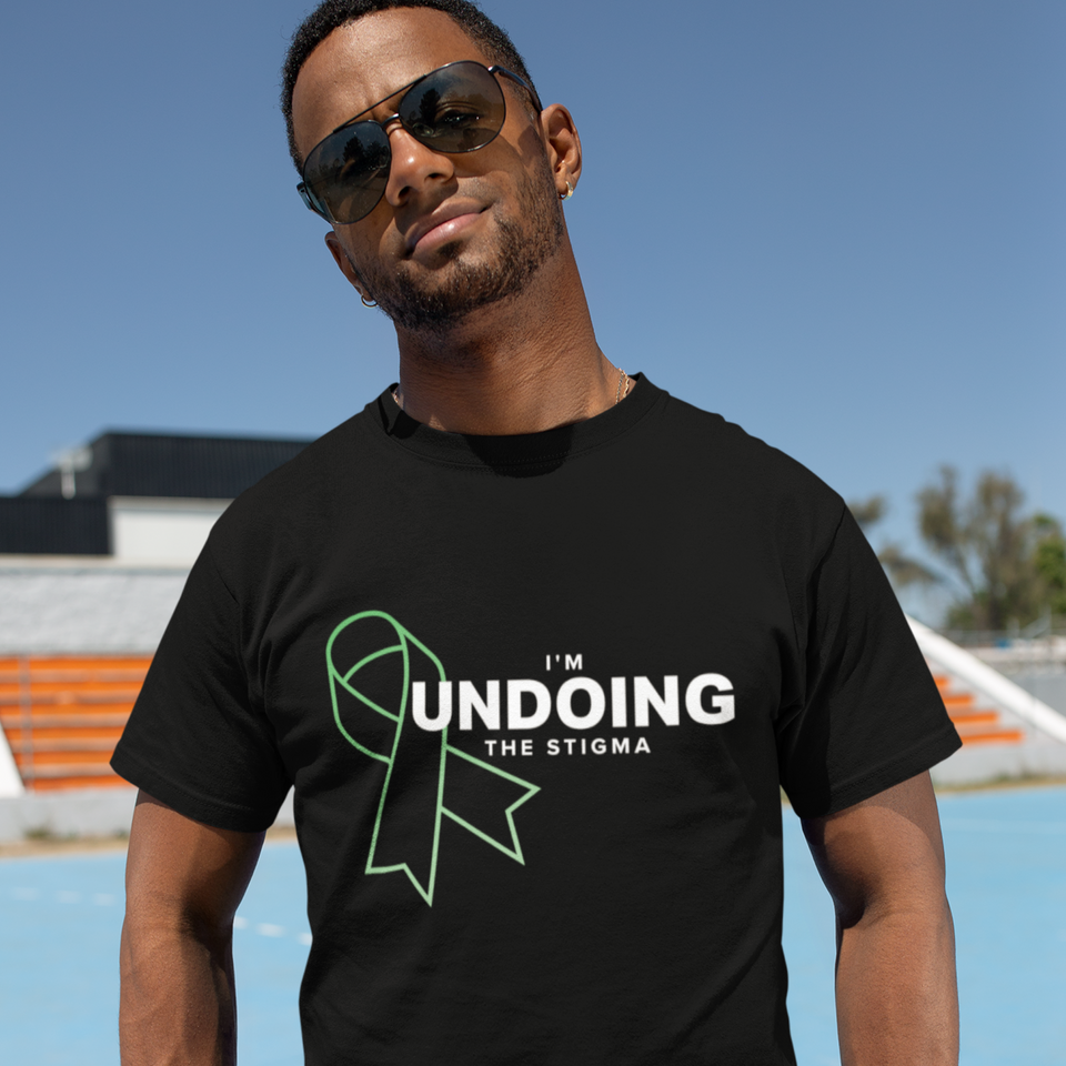 Male model posing outdoors wearing I'm Undoing the Stigma Mental Health Symbol - Black Unisex mental health awareness T-shirt