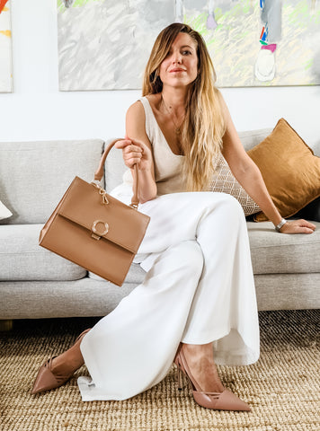 Founder - Sabrina sitting on a couch with her BrunchBag