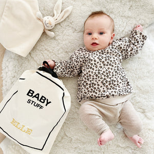 Baby laying on a bed with baby bag organizing bag.