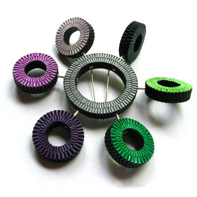 Brooch made of round handwoven elements that can independently rotate