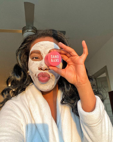 woman holding sand & sky product while wearing a face mask