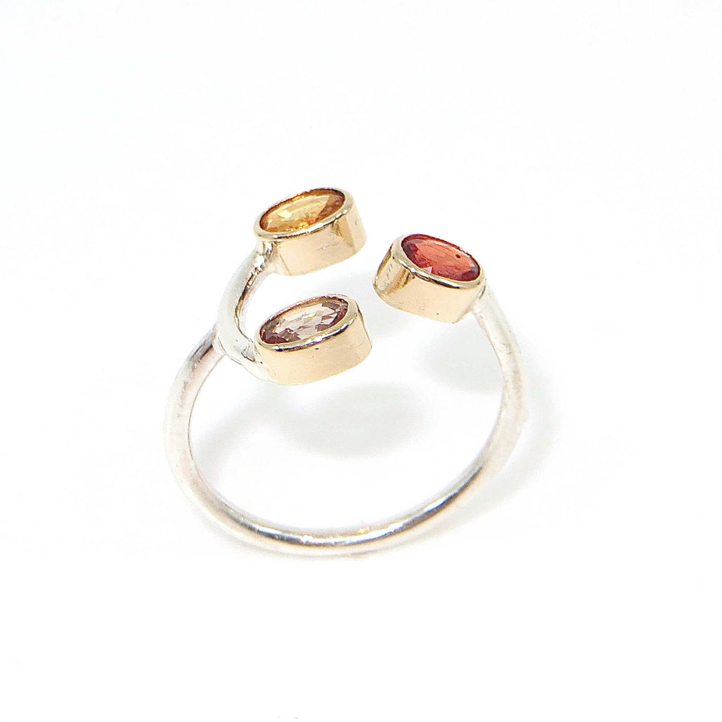 Open top ring.  Red oval sapphire on one side in gold bezel and golden and champagne color sapphires on other side.  Sterling ring band.