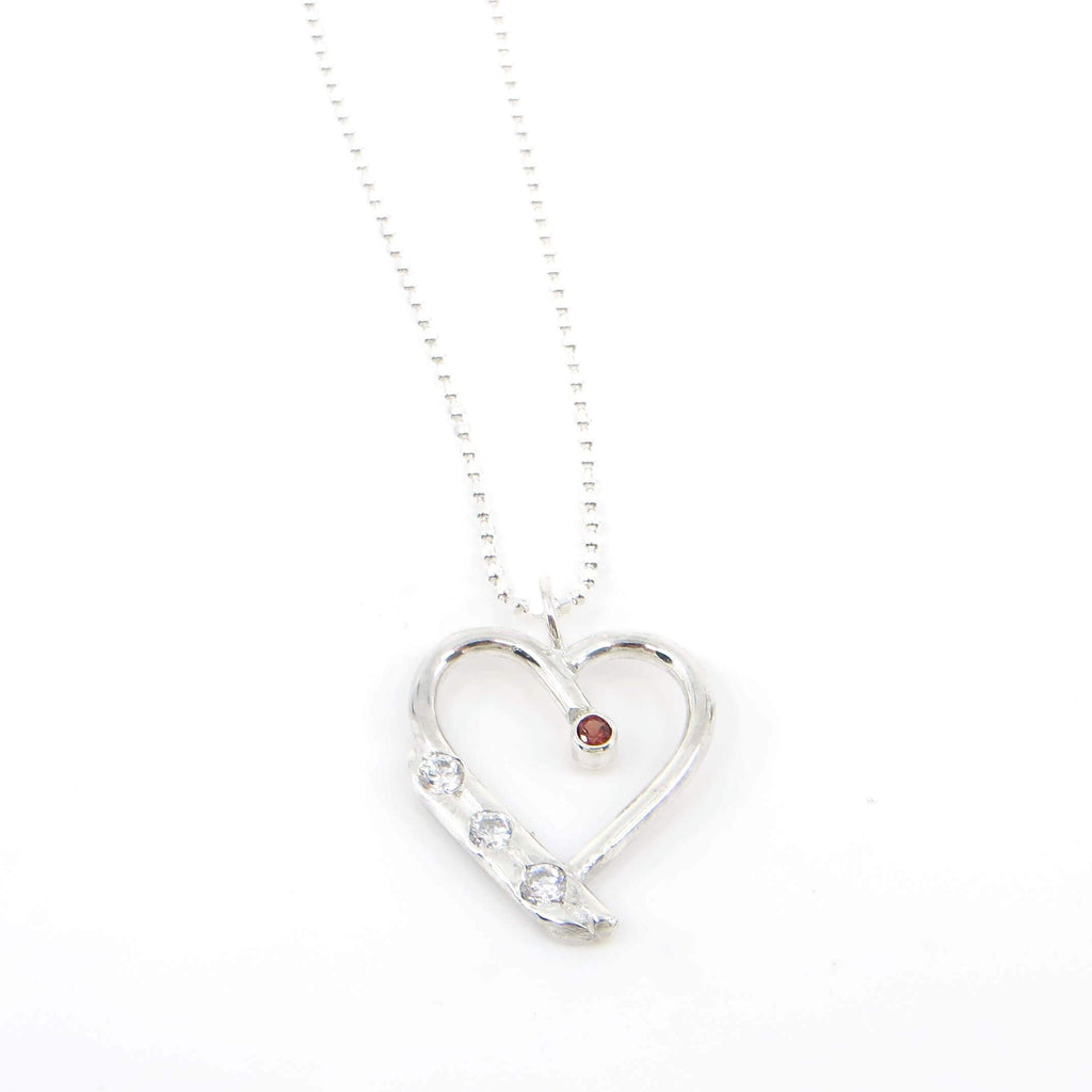 "Round sterling silver wire heart with tube set garnet suspended from vertex.  3 flush set cubic zirconia on double side wall of heart frame.  Heart is suspended from 16"" sterling silver diamond cut  bead chain."
