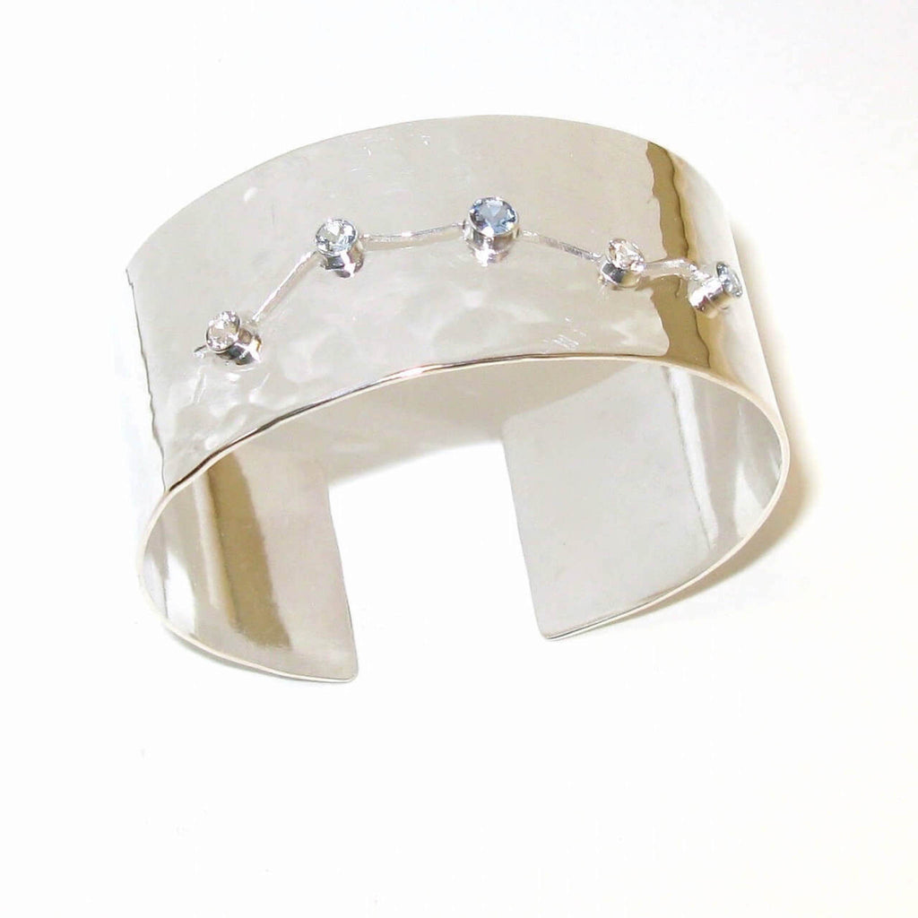Slightly hammered sterling silver wide cuff bracelet with meandering center open channel  of 5 tube set stones.  Center aquamarine. Two white topaz and two sky blue topaz.  Ice River Bracelet.