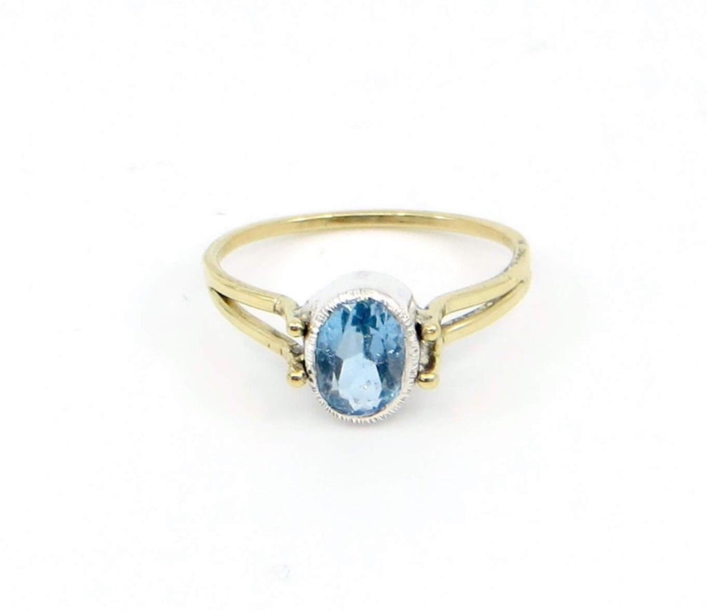 Oval Swiss Blue Topaz Ring. Oval set in fine silver with textured bezel top.  18k Royal yellow gold square wire two bands forming into one at bottom of finger.  Front view.