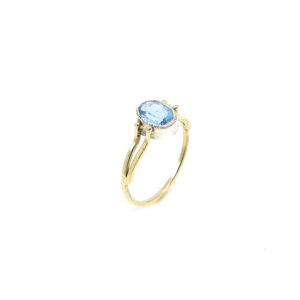 Oval Swiss Blue Topaz Ring. Oval set in fine silver with textured bezel top. 18k Royal yellow gold square wire two bands forming into one at bottom of finger.  Standing view.